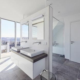 Großes Modernes Duschbad mit flächenbündigen Schrankfronten, weißen Schränken, offener Dusche, weißen Fliesen, Keramikfliesen, weißer Wandfarbe, Schieferboden, Aufsatzwaschbecken, grauem Boden, offener Dusche und brauner Waschtischplatte in Essen