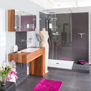 Mittelgroßes Modernes Duschbad mit Eckdusche, grauen Fliesen, grauer Wandfarbe, Einbauwaschbecken, Waschtisch aus Holz, grauem Boden, offener Dusche und brauner Waschtischplatte in Sonstige