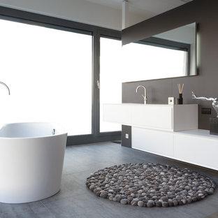 Kleines Modernes Badezimmer En Suite mit flächenbündigen Schrankfronten, weißen Schränken, freistehender Badewanne, braunen Fliesen, integriertem Waschbecken, Beton-Waschbecken/Waschtisch, grauem Boden und weißer Waschtischplatte in Sonstige