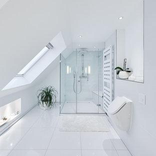 Modernes Badezimmer mit Bidet, weißen Fliesen, weißer Wandfarbe und Falttür-Duschabtrennung in Köln