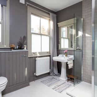 Ejemplo de cuarto de baño tradicional con ducha esquinera, baldosas y/o azulejos de cemento, paredes grises, suelo de madera pintada y lavabo con pedestal