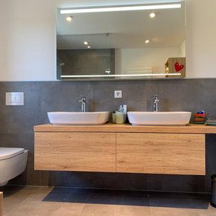 Неиссякаемый источник вдохновения для домашнего уюта: маленькая ванная комната в современном стиле с фасадами цвета дерева среднего тона, раздельным унитазом, серой плиткой, керамической плиткой, белыми стенами, полом из керамической плитки, душевой кабиной, настольной раковиной, столешницей из дерева, серым полом, открытым душем, сиденьем для душа, тумбой под две раковины, подвесной тумбой и многоуровневым потолком