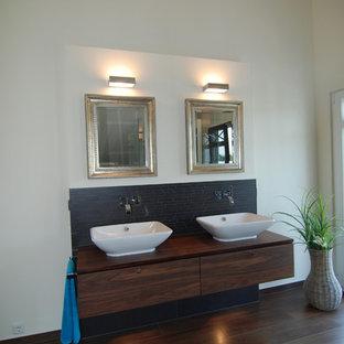 Foto di un'ampia stanza da bagno design con lavabo a bacinella, ante di vetro, vasca da incasso, doccia a filo pavimento, WC sospeso, piastrelle grigie, piastrelle in pietra e pavimento in gres porcellanato