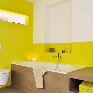 Foto di una stanza da bagno contemporanea con nessun'anta, ante marroni, vasca da incasso, WC sospeso e pareti gialle