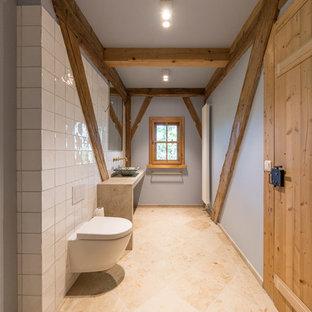 ミュンヘンの小さいラスティックスタイルのおしゃれなバスルーム (浴槽なし) (ドロップイン型浴槽、段差なし、壁掛け式トイレ、白いタイル、セラミックタイル、青い壁、ライムストーンの床、ベッセル式洗面器、ライムストーンの洗面台、ベージュの床、オープンシャワー) の写真