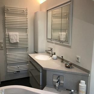 Esempio di una stanza da bagno contemporanea di medie dimensioni con ante lisce, ante bianche, vasca freestanding, WC sospeso, piastrelle grigie, piastrelle in metallo, pareti bianche, pavimento in vinile, lavabo rettangolare, top in superficie solida e pavimento nero