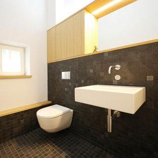 Mittelgroßes Modernes Duschbad Mit Flächenbündigen Schrankfronten, Hellen  Holzschränken, Wandtoilette, Schwarzen Fliesen, Weißer