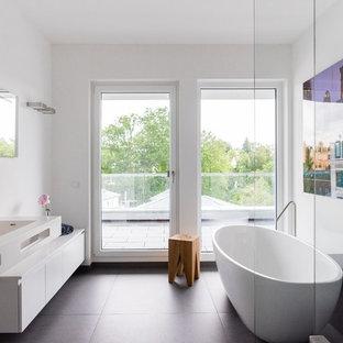 Mittelgroßes Modernes Duschbad mit flächenbündigen Schrankfronten, weißen Schränken, freistehender Badewanne, weißer Wandfarbe, Zementfliesen, integriertem Waschbecken, Falttür-Duschabtrennung und schwarzem Boden in Frankfurt am Main