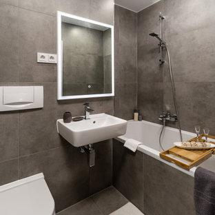 Modernes Duschbad mit Badewanne in Nische, Wandtoilette, grauen Fliesen, grauer Wandfarbe, Wandwaschbecken und grauem Boden in München