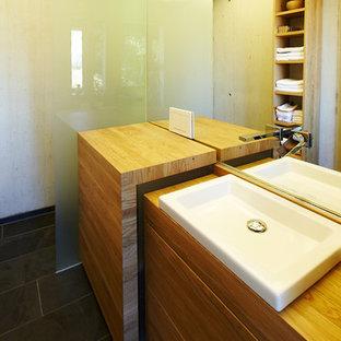 Modelo de cuarto de baño principal, clásico, de tamaño medio, con armarios con paneles lisos, puertas de armario de madera clara, ducha a ras de suelo, baldosas y/o azulejos con efecto espejo, paredes beige, suelo de baldosas de cerámica, lavabo sobreencimera, encimera de madera, suelo negro y ducha abierta
