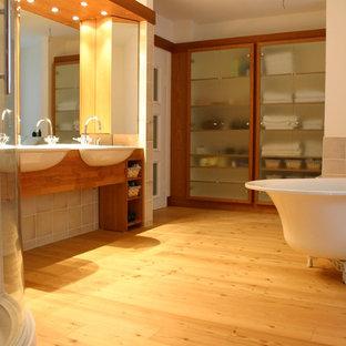 Ispirazione per una grande stanza da bagno chic con ante di vetro, ante in legno bruno, vasca freestanding, orinatoio, piastrelle in ceramica, parquet chiaro, lavabo a bacinella e top in legno