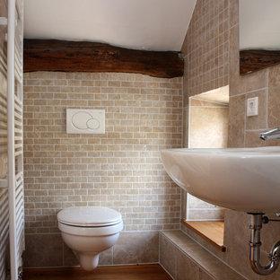 Idéer för att renovera ett litet lantligt badrum, med ett väggmonterat handfat, beige kakel, mellanmörkt trägolv, en vägghängd toalettstol och stenkakel