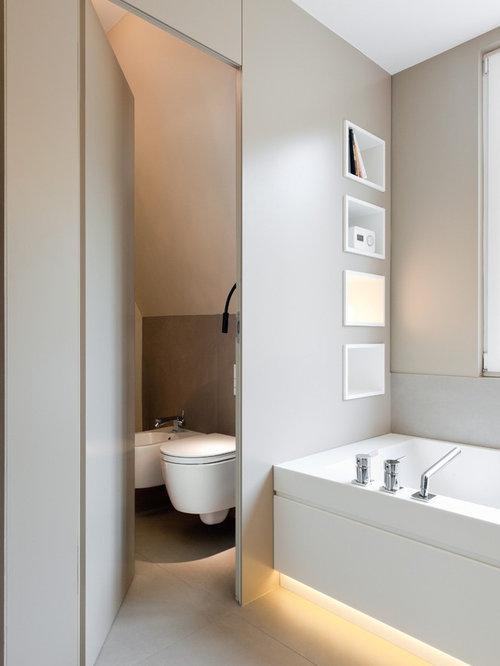 Mittelgroßes Modernes Badezimmer Mit Badewanne In Nische, Wandtoilette,  Grauer Wandfarbe, Beigefarbenen Fliesen Und