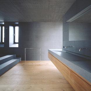 Immagine di un'ampia stanza da bagno moderna con ante lisce, ante in legno scuro, piastrelle grigie, piastrelle di cemento, parquet chiaro, lavabo integrato e top alla veneziana