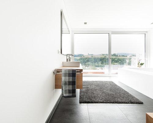 Großes Modernes Badezimmer Mit Hellbraunen Holzschränken, Schwarzen Fliesen,  Weißer Wandfarbe, Aufsatzwaschbecken Und Waschtisch