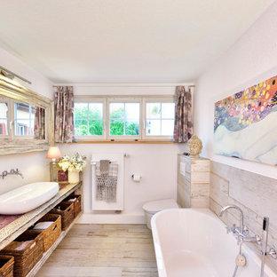 Ispirazione per una stanza da bagno stile shabby di medie dimensioni con vasca da incasso, WC sospeso, pareti bianche, lavabo a bacinella, top in legno, nessun'anta, ante con finitura invecchiata, piastrelle beige, pavimento beige e top beige