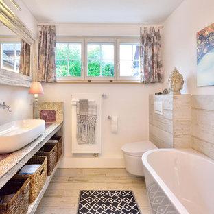 Kleines Shabby-Chic-Style Duschbad mit offenen Schränken, Schränken im Used-Look, freistehender Badewanne, Wandtoilette, beigefarbenen Fliesen, weißer Wandfarbe, hellem Holzboden, Aufsatzwaschbecken, Waschtisch aus Holz, beigem Boden und beiger Waschtischplatte in Sonstige