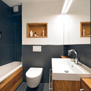 Imagen de cuarto de baño con ducha, actual, pequeño, con armarios con paneles empotrados, puertas de armario de madera oscura, bañera encastrada, sanitario de dos piezas, baldosas y/o azulejos negros, baldosas y/o azulejos de piedra, paredes blancas, suelo de terrazo, lavabo sobreencimera, encimera de madera y suelo negro