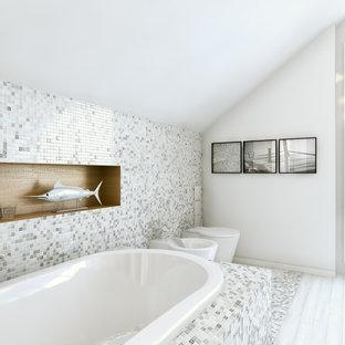 Modernes Badezimmer mit Einbaubadewanne, Wandtoilette mit Spülkasten, grauen Fliesen, Mosaikfliesen, weißer Wandfarbe, hellem Holzboden und weißem Boden in Düsseldorf