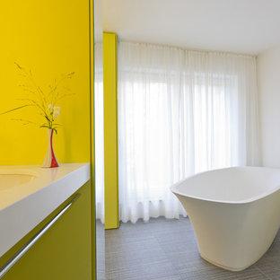 Idee per una piccola stanza da bagno minimal con lavabo sospeso, vasca freestanding, doccia a filo pavimento, pareti gialle, pavimento in gres porcellanato e ante gialle