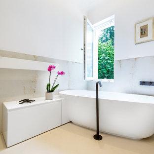 Mittelgroßes Shabby-Chic-Style Badezimmer mit freistehender Badewanne, beigefarbenen Fliesen, beigem Boden, flächenbündigen Schrankfronten, weißen Schränken, offener Dusche, Wandtoilette, Keramikfliesen, beiger Wandfarbe, integriertem Waschbecken, Mineralwerkstoff-Waschtisch, offener Dusche und weißer Waschtischplatte in Köln