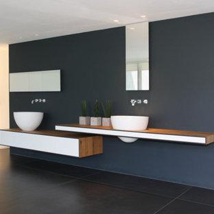 Großes Modernes Badezimmer mit Waschtisch aus Holz, freistehender Badewanne, grauer Wandfarbe, flächenbündigen Schrankfronten, weißen Schränken, Schieferboden, Aufsatzwaschbecken und brauner Waschtischplatte in Köln