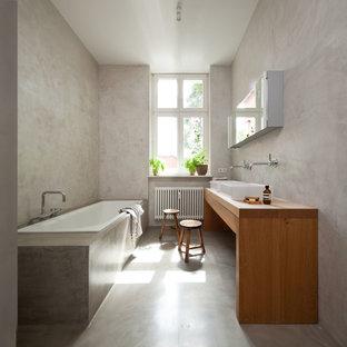 Mittelgroßes Modernes Badezimmer mit Einbaubadewanne, grauer Wandfarbe, Betonboden, Aufsatzwaschbecken, Waschtisch aus Holz und brauner Waschtischplatte in Berlin