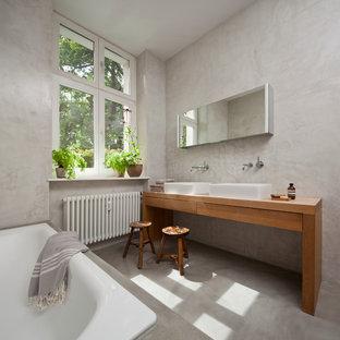 Modelo de cuarto de baño contemporáneo, grande, con armarios con paneles lisos, puertas de armario de madera oscura, bañera encastrada, paredes grises, suelo de cemento, lavabo sobreencimera, encimera de madera y encimeras marrones
