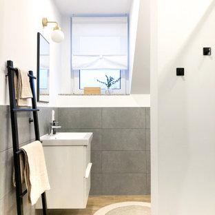 Идея дизайна: ванная комната среднего размера в современном стиле с белыми фасадами, душем без бортиков, серой плиткой, керамической плиткой, белыми стенами, полом из плитки под дерево, душевой кабиной, настольной раковиной, коричневым полом, душем с раздвижными дверями и белой столешницей