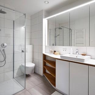 Kleines Nordisches Duschbad mit flächenbündigen Schrankfronten, weißen Schränken, Eckdusche, Wandtoilette, weißen Fliesen, Travertinfliesen, weißer Wandfarbe, Einbauwaschbecken, beigem Boden, Falttür-Duschabtrennung und weißer Waschtischplatte in Stuttgart