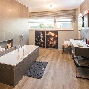 Modernes Badezimmer mit flächenbündigen Schrankfronten, schwarzen Schränken, Einbaubadewanne, braunem Holzboden, integriertem Waschbecken, braunem Boden und weißer Waschtischplatte in Sonstige