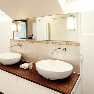 Diseño de cuarto de baño contemporáneo, de tamaño medio, con sanitario de pared, baldosas y/o azulejos de cerámica, paredes beige, suelo de bambú, lavabo sobreencimera, armarios con paneles lisos, puertas de armario blancas, baldosas y/o azulejos beige, encimera de madera y encimeras marrones