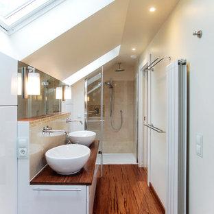 Новый формат декора квартиры: ванная комната среднего размера в современном стиле с плоскими фасадами, белыми фасадами, душем в нише, бежевой плиткой, керамической плиткой, бежевыми стенами, полом из бамбука, настольной раковиной и столешницей из дерева
