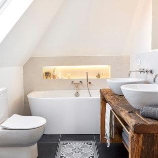 Kleines Country Badezimmer En Suite mit Toilette mit Aufsatzspülkasten, weißen Fliesen, weißer Wandfarbe, Aufsatzwaschbecken, Waschtisch aus Holz, schwarzem Boden, brauner Waschtischplatte, offenen Schränken, dunklen Holzschränken, freistehender Badewanne, Keramikboden, Duschbadewanne und offener Dusche in Sonstige