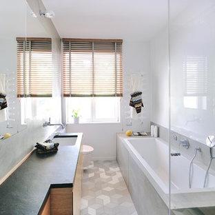 Kleines Modernes Duschbad mit flächenbündigen Schrankfronten, bodengleicher Dusche, Wandtoilette, weißer Wandfarbe, Waschtisch aus Holz, grauem Boden, Falttür-Duschabtrennung, grauer Waschtischplatte, hellbraunen Holzschränken, Einbaubadewanne, grauen Fliesen und Unterbauwaschbecken in München