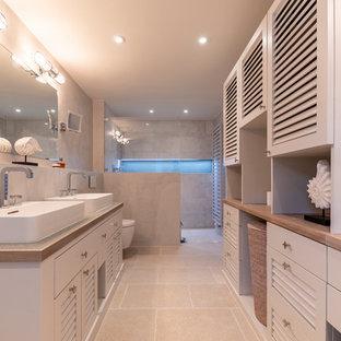 Immagine di una grande stanza da bagno padronale stile marinaro con ante a persiana, ante grigie, doccia a filo pavimento, WC sospeso, pareti grigie, pavimento in pietra calcarea, lavabo a bacinella, top piastrellato, pavimento beige, doccia aperta e top grigio