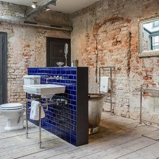 Ejemplo de cuarto de baño con ducha, urbano, de tamaño medio, con bañera exenta, baldosas y/o azulejos azules, baldosas y/o azulejos de cerámica, lavabo tipo consola, sanitario de dos piezas, suelo de madera clara, suelo gris, combinación de ducha y bañera, paredes rojas y encimera de acrílico