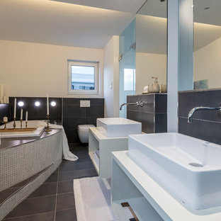 Großes Modernes Duschbad mit offenen Schränken, weißen Schränken, Einbaubadewanne, Duschnische, Toilette mit Aufsatzspülkasten, weißer Wandfarbe, Aufsatzwaschbecken, grauem Boden, Falttür-Duschabtrennung, weißer Waschtischplatte und schwarzen Fliesen in Frankfurt am Main