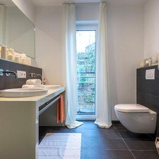 Mittelgroßes Modernes Duschbad mit Toilette mit Aufsatzspülkasten, schwarzen Fliesen, grauen Fliesen, weißer Wandfarbe, Aufsatzwaschbecken, grauem Boden und beiger Waschtischplatte in Frankfurt am Main
