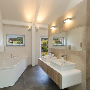 Foto de cuarto de baño contemporáneo, grande, con armarios con paneles lisos, puertas de armario de madera clara, bañera esquinera, ducha a ras de suelo, baldosas y/o azulejos beige, baldosas y/o azulejos de cerámica, paredes blancas, suelo de baldosas de porcelana, lavabo de seno grande, sanitario de pared y encimera de acrílico