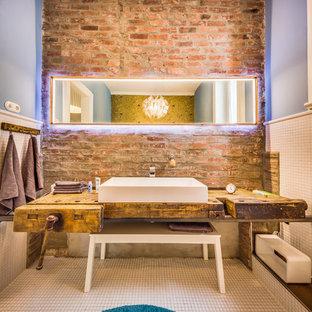 Imagen de cuarto de baño de estilo de casa de campo, de tamaño medio, con baldosas y/o azulejos blancos, baldosas y/o azulejos de cerámica, paredes azules, suelo de baldosas de cerámica, lavabo sobreencimera y encimera de madera