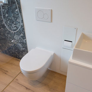 Mittelgroßes Modernes Duschbad mit weißen Schränken, bodengleicher Dusche, Wandtoilette, weißer Wandfarbe, braunem Holzboden, Aufsatzwaschbecken, braunem Boden, offener Dusche, weißer Waschtischplatte, flächenbündigen Schrankfronten, schwarz-weißen Fliesen, Kieselfliesen und Mineralwerkstoff-Waschtisch in Sonstige