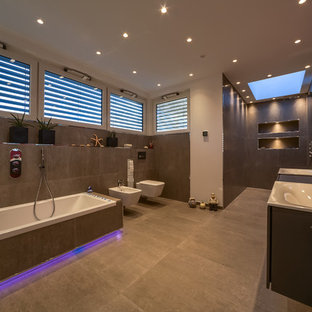 Inspiration for a contemporary master bathroom in Essen with flat-panel cabinets, brown cabinets, a drop-in tub, an alcove shower, a bidet, gray tile, stone tile, red walls, concrete floors, a drop-in sink, wood benchtops, grey floor, an open shower and brown benchtops.