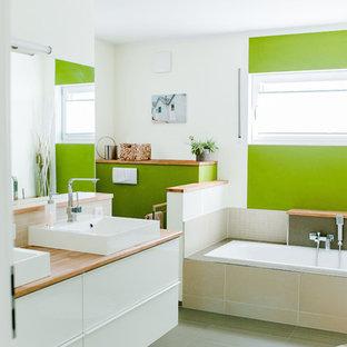 Mittelgroßes Modernes Badezimmer mit weißen Schränken, Einbaubadewanne, offener Dusche, Wandtoilette mit Spülkasten, beigefarbenen Fliesen, Keramikfliesen, grüner Wandfarbe, Porzellan-Bodenfliesen, Aufsatzwaschbecken, Mineralwerkstoff-Waschtisch, grauem Boden und brauner Waschtischplatte in Nürnberg