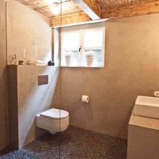 Imagen de cuarto de baño con ducha, rústico, con ducha a ras de suelo, sanitario de pared, paredes grises, suelo de baldosas tipo guijarro y lavabo sobreencimera