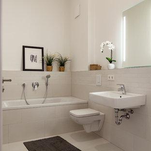 Immagine di una piccola stanza da bagno con doccia minimal con WC sospeso, pareti beige, lavabo sospeso, pavimento beige, vasca da incasso, vasca/doccia, piastrelle a listelli, pavimento con piastrelle in ceramica e doccia aperta