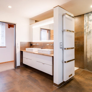 Großes Asiatisches Duschbad mit flächenbündigen Schrankfronten, weißen Schränken, braunen Fliesen, weißer Wandfarbe, Aufsatzwaschbecken, Waschtisch aus Holz, braunem Boden und beiger Waschtischplatte in Sonstige