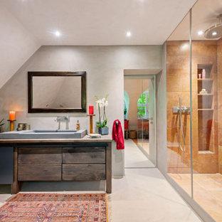 Großes Kolonialstil Badezimmer mit dunklen Holzschränken, Eckbadewanne, bodengleicher Dusche, beigefarbenen Fliesen, Travertinfliesen, beiger Wandfarbe, Betonboden, Aufsatzwaschbecken, Beton-Waschbecken/Waschtisch, beigem Boden, offener Dusche, brauner Waschtischplatte, Einzelwaschbecken, freistehendem Waschtisch und gewölbter Decke in München