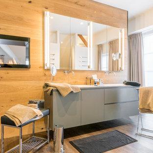 Foto di una grande stanza da bagno con doccia bohémian con ante lisce, ante grigie, vasca da incasso, WC sospeso, pareti bianche, pavimento in legno massello medio e lavabo da incasso