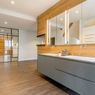 Großes Rustikales Duschbad mit flächenbündigen Schrankfronten, Laminat-Waschtisch, braunem Boden, grauen Schränken, weißer Wandfarbe, Einbaubadewanne, Wandtoilette, braunem Holzboden und Einbauwaschbecken in Hannover